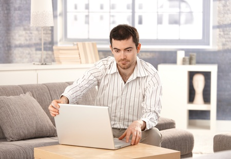 Young man browsing Internet at home, sitting on sofa, looking at screen. Stock Photo - 8558309