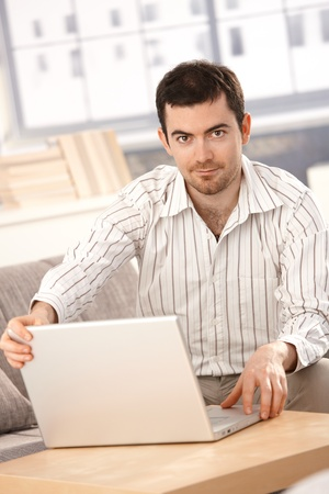 Young man working at home, sitting on sofa, using laptop. Stock Photo - 8549506