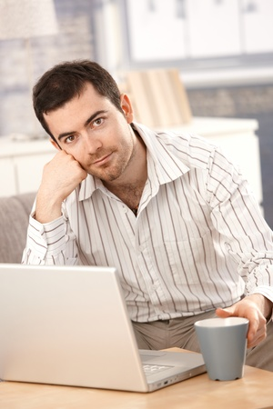 Young male working at home, sitting on sofa, using laptop. Stock Photo - 8558321