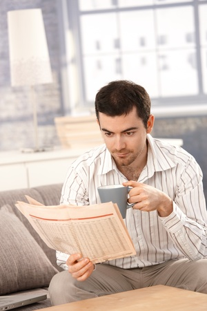 Young man reading newspaper, sitting on sofa, drinking tea. photo
