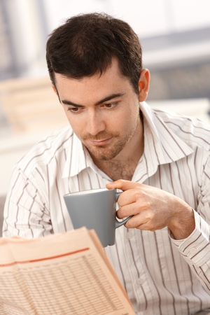 Young man reading newspaper, drinking tea at home. Stock Photo - 8549624