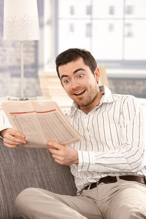 Young male reading lottery numbers from newspaper, smiling happily. Stock Photo - 8549855