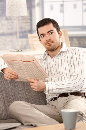 Young man reading newspaper, sitting on sofa at home smiling. Stock Photo - 8552194