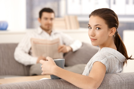 Young attractive woman sitting on sofa at home, man reading newspaper in the background. photo
