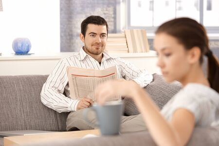 Young couple sitting on sofa in living room, man reading newspaper, woman drinking tea. Stock Photo - 8549797