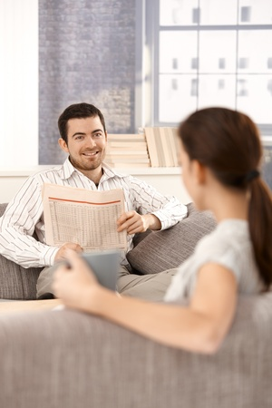 Young couple sitting on sofa in living room, man reading newspaper, woman drinking tea. photo