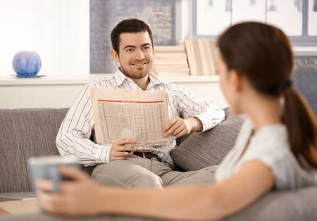 Young couple sitting on sofa in living room, man smiling at woman and reading newspaper, woman drinking tea. photo