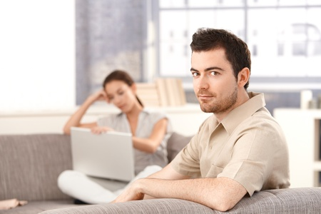 Young man sitting on sofa at home, woman using laptop in the background. photo