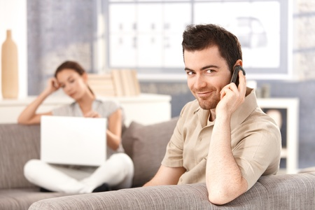 Young man sitting on sofa at home, talking on mobile, smiling, woman using laptop in the background. photo