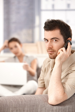 Young man sitting on sofa at home, talking on mobile, woman using laptop in the background. photo