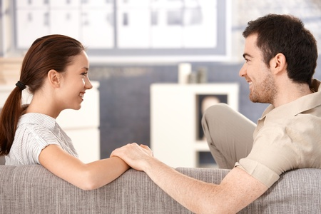 happily: Young couple sitting on sofa at home, holding hands, smiling happily each other. Stock Photo