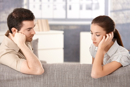 Young couple sitting on sofa at home sadly after quarrelling. photo