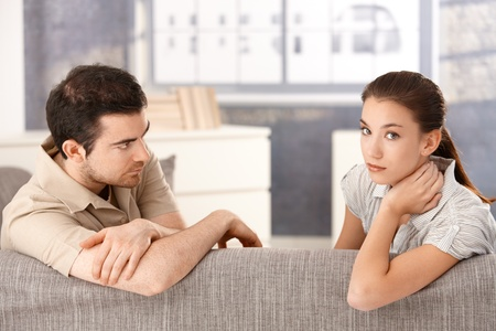 sadly: Young couple sitting on sofa at home sadly after quarrelling.