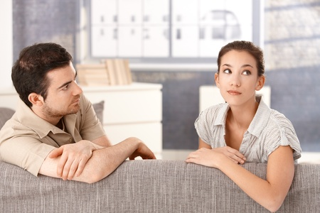 Young couple sitting on sofa at home in bad mood after quarrelling. photo