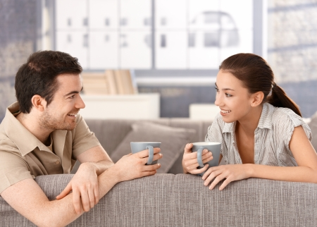 tea cosy: Happy couple sitting on sofa at home, drinking tea, smiling at each other. Stock Photo