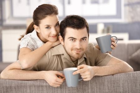 amigos abrazandose: Feliz pareja sentado en el sof� en el hogar, beber t�, sonriendo.