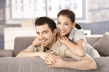 cuddles: Young couple smiling happily on sofa, hugging each other at home.