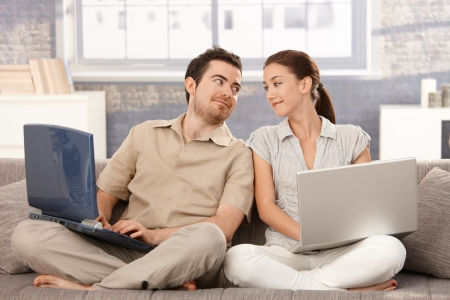 a pair: Young couple sitting on sofa at home, using laptop, smiling at each other. Stock Photo