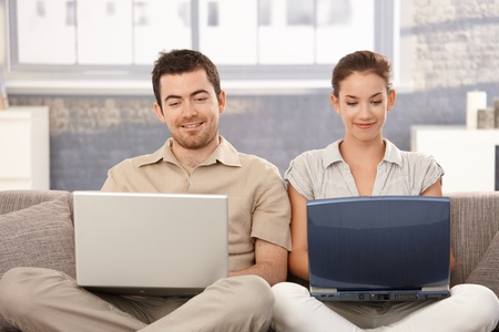 Young couple sitting on sofa at home, browsing internet on separate laptops, smiling, having fun. photo