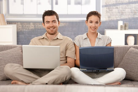 Happy couple sitting on sofa at home, browsing internet on separate laptops, smiling, having fun. Stock Photo