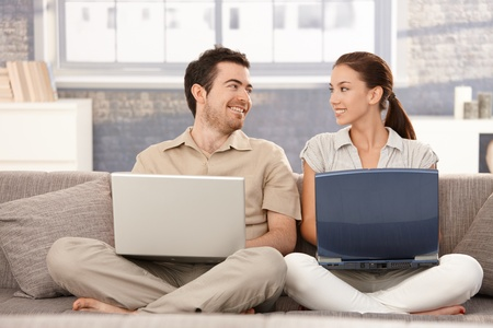 Happy couple sitting on sofa at home, browsing internet on separate laptops, smiling, having fun.