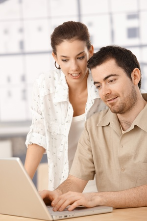 Young couple using laptop together at home, browsing internet, smiling. photo