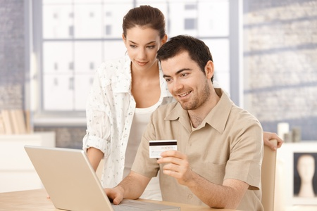 Happy couple using laptop, shopping online at home, using credit card. Stock Photo - 8549433