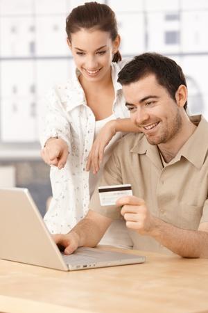prestar atencion: Feliz pareja usa portátil, compras en línea en el hogar, mediante tarjeta de crédito, que se divierten. Foto de archivo