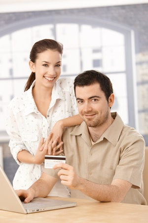 Happy couple using laptop, shopping online at home, using credit card. photo