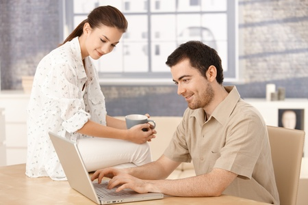 Young couple browsing internet at home, woman sitting on table, drinking tea, man typing. photo