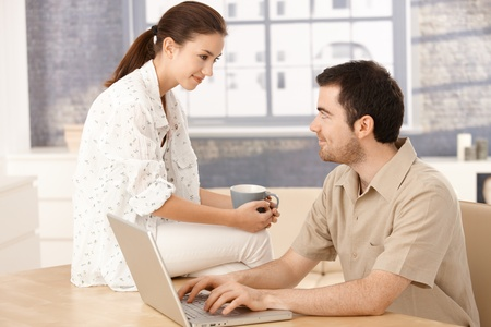 Young couple browsing internet at home, woman sitting on table, drinking tea, man typing, smiling at each other. photo