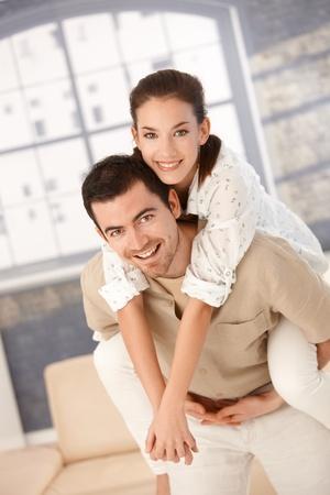 amigos abrazandose: Feliz pareja que se divierten en el hogar, mujer de explotaci�n del hombre por su vuelta, sonriendo.
