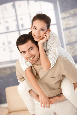 enjoy space: Happy young couple having fun at home, man holding woman on his back, smiling. Stock Photo