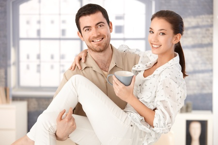 Happy young man holding woman in his arms, woman drinking tea, smiling. photo