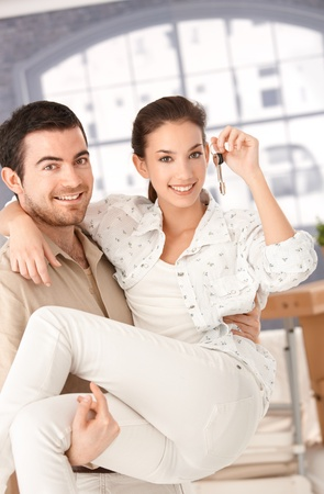 Happy young couple moving to new home, smiling, holding keys in hand. photo