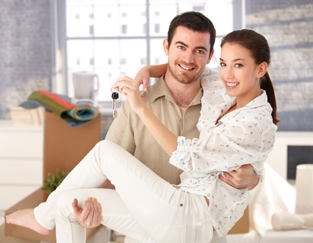 Young couple smiling happily in new house, holding keys in hand, mess around. photo