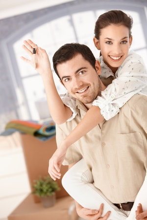 moving box: Happy couple moving house, boxes around, holding keys, smiling, having fun. Stock Photo