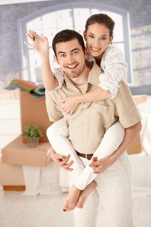 amigos abrazandose: Feliz pareja celebrando nuevas claves de la casa, sonriente, explotaci�n de la mano.