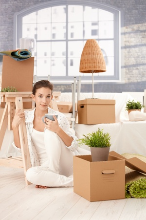 Portrait of young attractive female moving to new house, sitting on floor, drinking tea, boxes around. photo