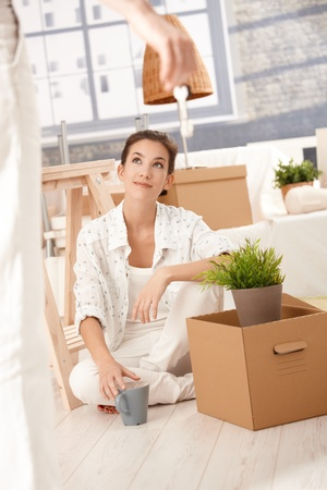 Young couple moving home, woman sitting on floor with boxes around, man hanging keys front of her. photo