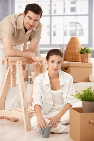 Young couple moving home, sitting on floor, boxes around, smiling, drinking tea. photo