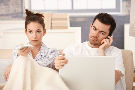 listening back: Young couple in bed, man using laptop and mobile, woman watching television.