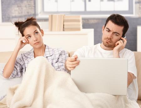 bored man: Giovane coppia a letto, uomo utilizzando il computer portatile e mobile, donna annoiato.