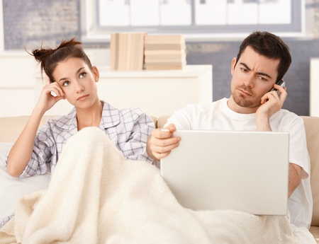 bored woman: Young couple in bed, man using laptop and mobile, woman bored. Stock Photo