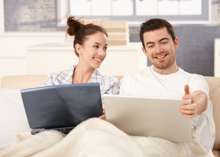 looking at each other: Young couple working at home in bed, using laptop, smiling. Stock Photo