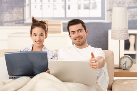 Happy young couple browsing internet in bed at home, smiling. photo