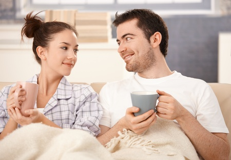 nighty: Happy young couple drinking tea in bed, smiling at each other.