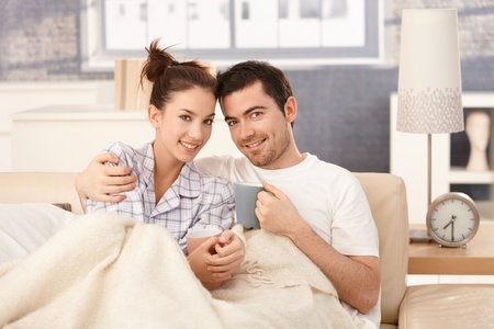 Young couple drinking tea in bed, hugging each other, smiling happily. photo