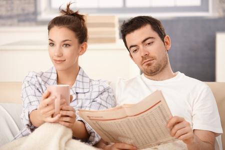 tea cosy: Young couple sitting in bed, man reading newspaper, woman drinking tea, smiling. Stock Photo