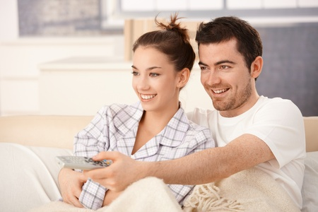 each: Happy couple watching television in bed, hugging each other, smiling. Stock Photo